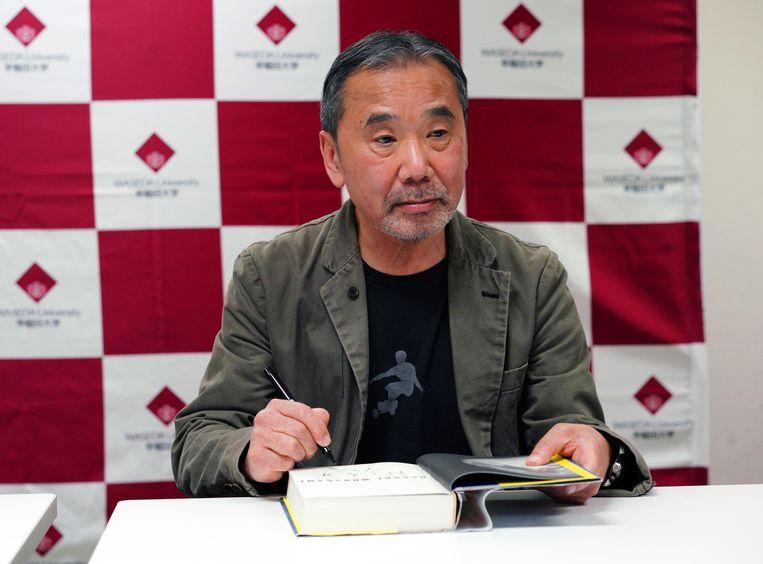 De Japanse schrijver Haruki Murakami signeert een boek tijdens de persconferentie. Beeld AP