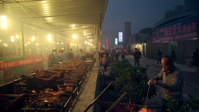 Een barbecue in de sterk vervuilde Chinese miljoenenstad Chongqing. Zo'n 25 kilometer verderop wordt nu de eco-satd Yuelai gebouwd. Beeld Getty