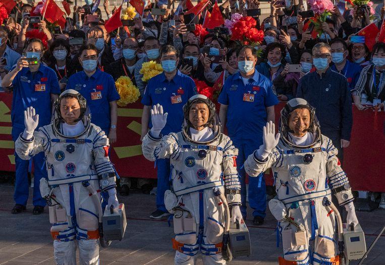 De drie Chinese taikonauten, Nie Haisheng, Liu Boming, and Tang Hongbo, zwaaien voor hun vertrek naar het ruimtestation.  Beeld Getty Images