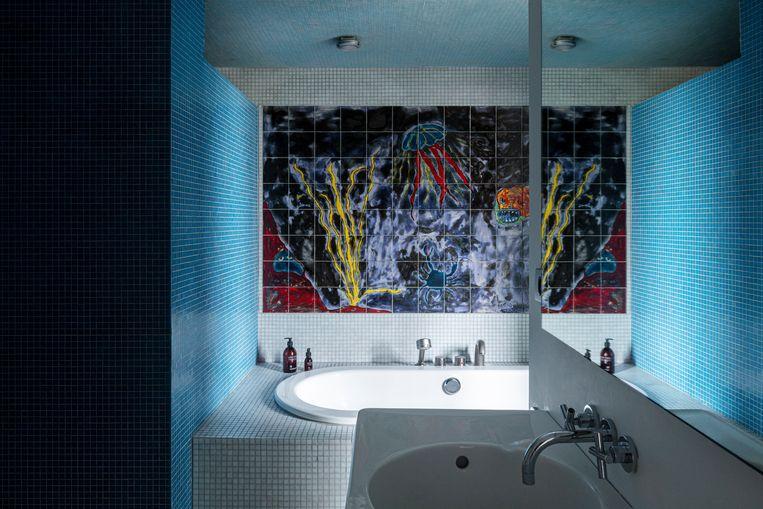 In de badkamer trekt het onderwatertafereel alle aandacht.Het tegeltableau is een werk van kunstenaar Mirko Krabbé. Beeld Tim van de Velde