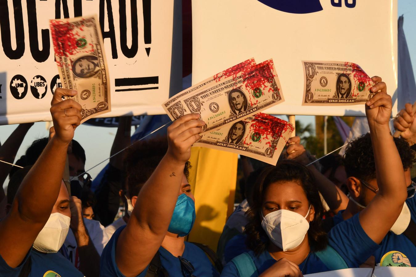 Demonstranten hadden met rode verf besmeurde nepdollarbiljetten meegenomen. Een dollar is de vermeende meerprijs die het ministerie vroeg per dosis van het vaccin.