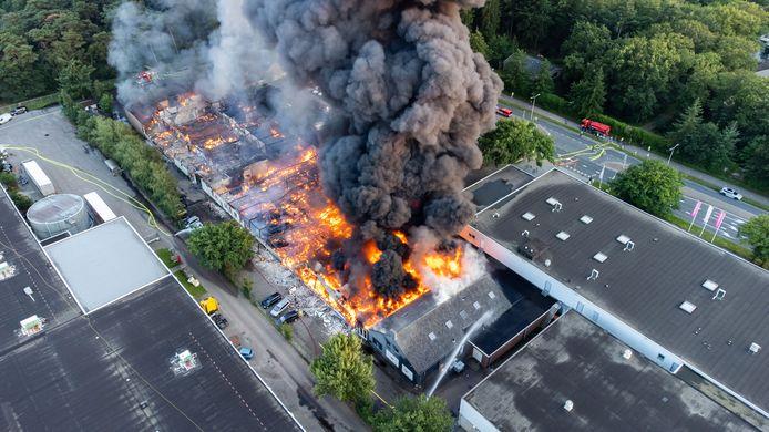 Het pand is compleet verloren gegaan, de brandweer probeert de omliggende panden te redden. Rechts het pand van Leen Bakker, links de Kwantum.