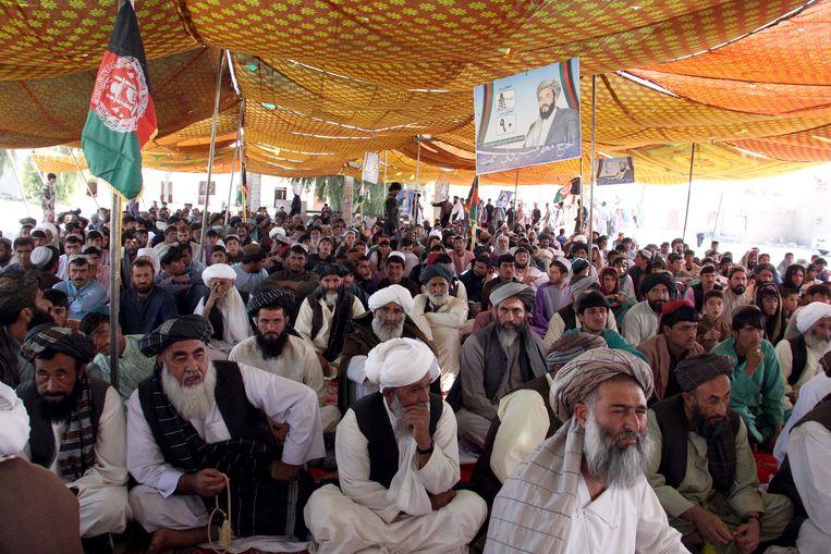 Afghanen luisteren naar kandidaat Mir Wali, in Helmand, Afghanistan. Beeld EPA