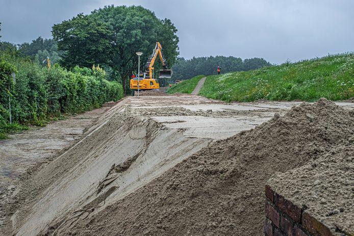 Een flinke lading zand moet de dijk in Gennep sterk genoeg maken om het hoogwater tegen te houden.