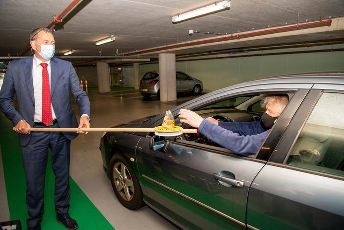 Raadslid Wim Kloekhorst van OpKoers.nu heeft in de parkeerkelder zijn stem uitgebracht op nieuwe wethouder Nico Lansink Rotgerink. Bij het uitrijden van de parkeerkelder krijgt hij wat lekkers mee naar huis van burgemeester Maarten Offinga, die de versnapering coronaproof aanbiedt.