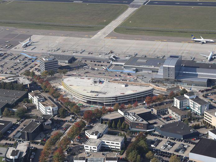 Links op de voorgrond het (witte) kantoorgebouw en de magazijnruimte daarachter dat Airport wil slopen om het perceel in te kunnen zetten als tijdelijk parkeerterrein.