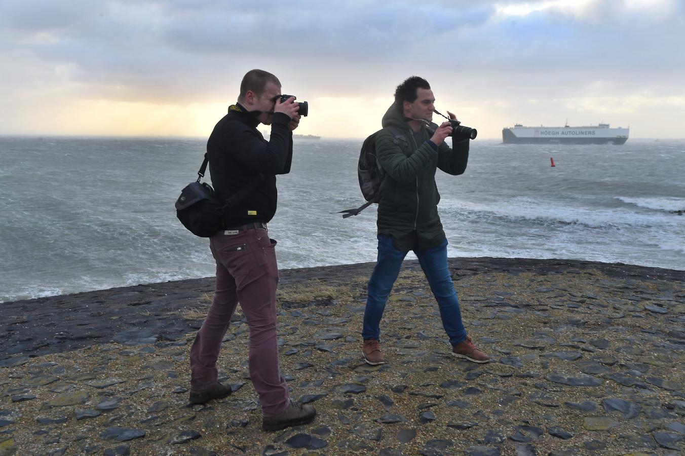 Gijs de Reijke en  Paul Begijn vliegen de deur uit om foto's in de storm te maken.