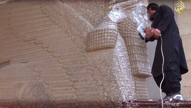 A militant uses a power tool to destroy a winged-bull Assyrian protective deity at the Ninevah Museum in Mosul, Iraq. Beeld AP