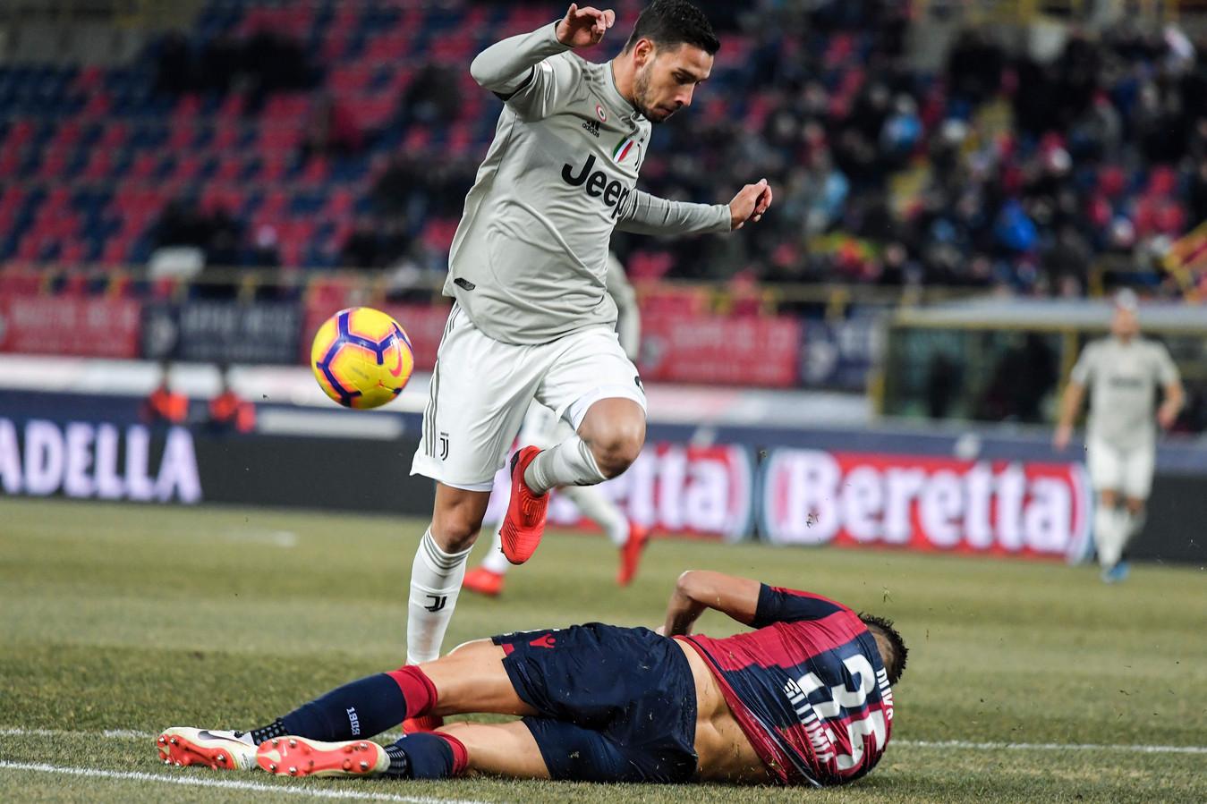 Mattia De Sciglio van Juventus probeert over Bologna-verdediger Mitchell Dijks heen te springen.