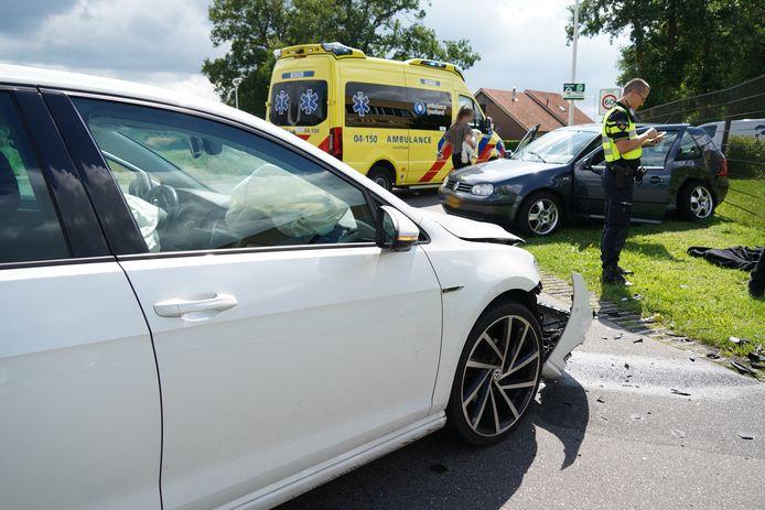 De zwarte auto (rechts) kwam na het ongeval tegen een hek te staan.