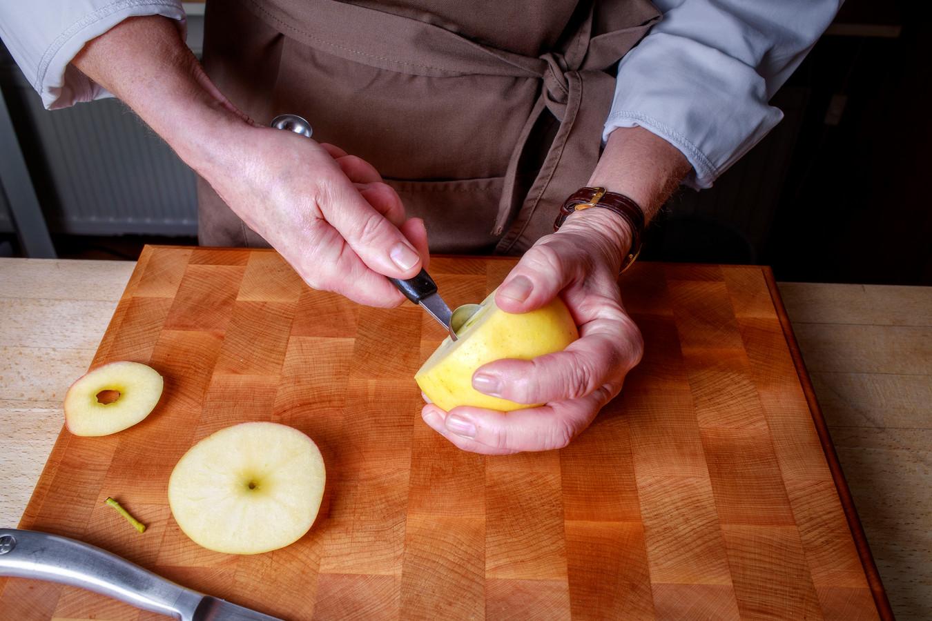 Carla Kentgens maakt wild zwijn klaar. De appel wordt gesneden en uitgehold voor de vulling. Foto: Dolph Cantrijn