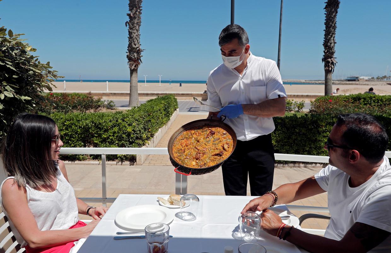 Een ober serveert paëlla aan het strand van Valencia.  Beeld EPA
