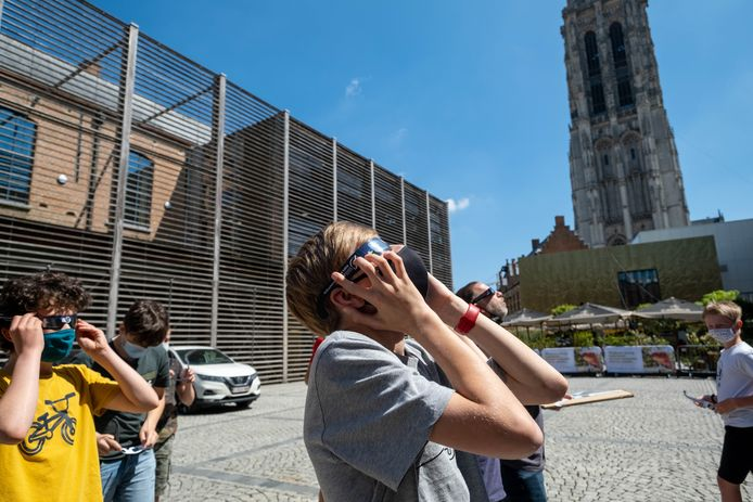 MECHELEN Leerlingen van het eerste jaar STEM Wetenschappen van TSM kijken naar de zonsverduistering vanop het Cultuurplein aan de voet van de Sint-Romboutstoren.