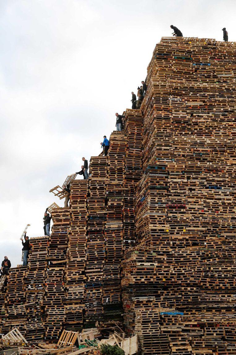 Op het Zuiderstrand worden op oudjaarsdag pallets gestapeld voor het vreugdevuur van Duindorp. Beeld anp