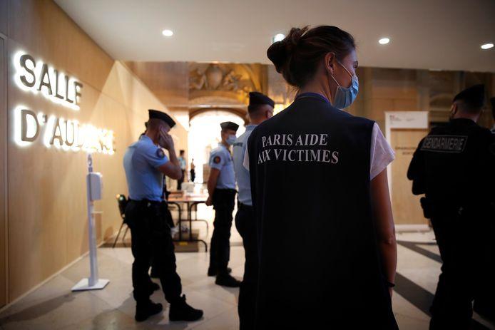 """Le personnel du """"soutien psychologique aux victimes"""" se tient devant la salle d'audience du procès des attentats de Paris de 2015 au palais de justice de Paris."""