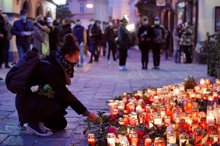 Een vrouw steekt donderdag in Wenen een kaars aan bij een geïmproviseerde gedenkplaats op de plek van de aanslag. Beeld Getty