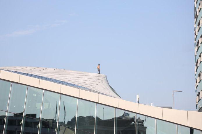 Een man staat op het dak van het centraal station in Arnhem.