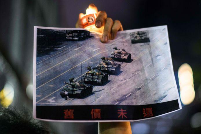 Een man houdt tijdens de jaarlijkse herdenkingsdienst een foto omhoog van het beroemde beeld van een man die in zijn eentje voor een tank staat tijdens de protesten op het Plein van de Hemelse Vrede op 5 juni 1989.