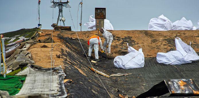 Medewerkers van Hein Heun voeren in grote plastic zakken de verbande afvalresten af.
