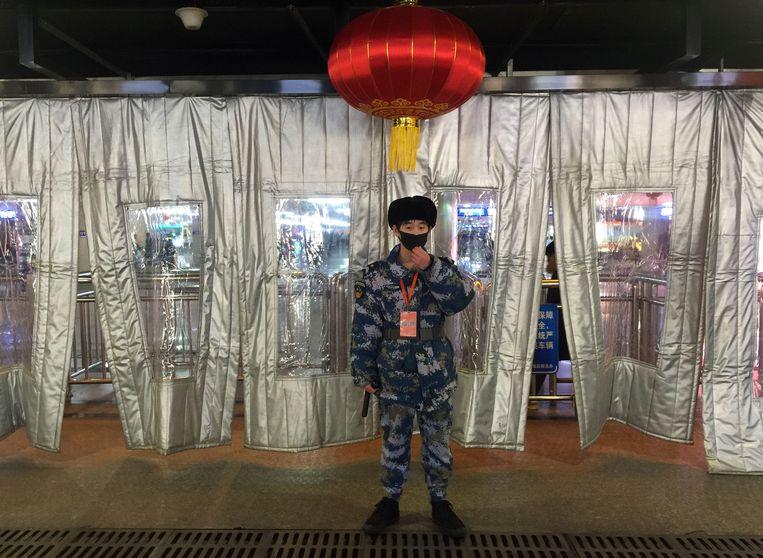 Bewaker met masker staat buiten de security check op een treinstation in Peking.  Beeld REUTERS