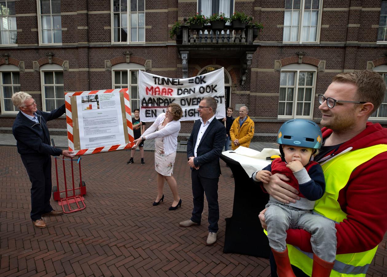 Omwonenden van nieuwe spoortunnel, met links Jan Manders, overhandigen burgemeester Greet Buter een hele lading handtekeningen omdat ze zich zorgen maken.