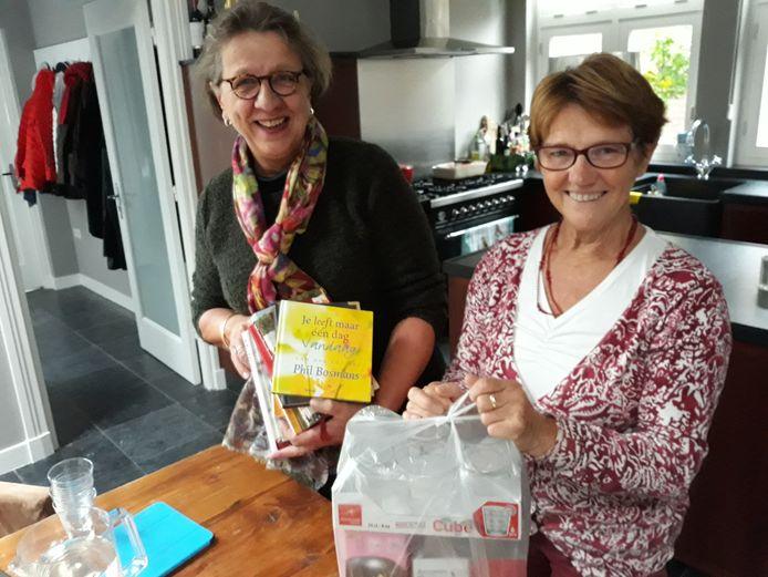 Willemien Mommersteeg-Willekens (links) en Anny van Zandbeek (initiatiefneemsters van Parnassia) tonen enkele dozen met nieuwe glazen. Door een sympathisant voor de deur neergezet, bedoeld voor het hospice.