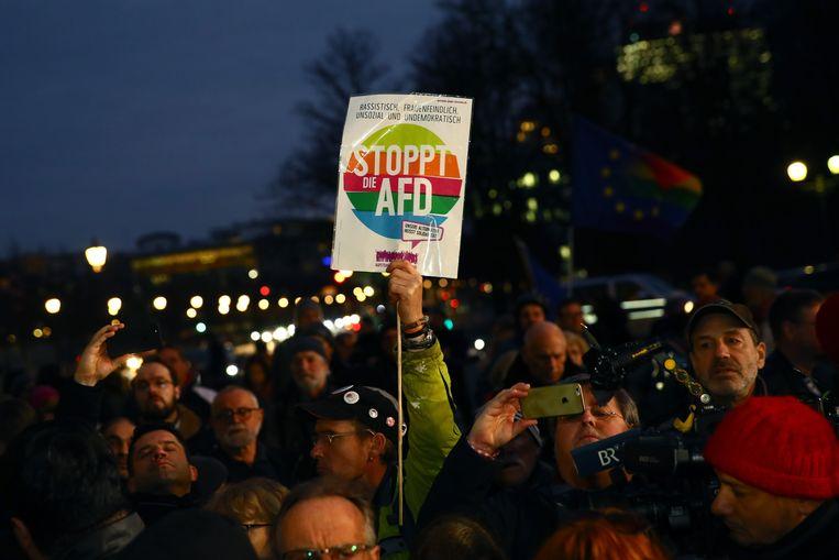 Een man houdt een bord omhoog met daarop 'Stop AFD' tijdens een wake voor de slachtoffers van Hanau Beeld Getty Images