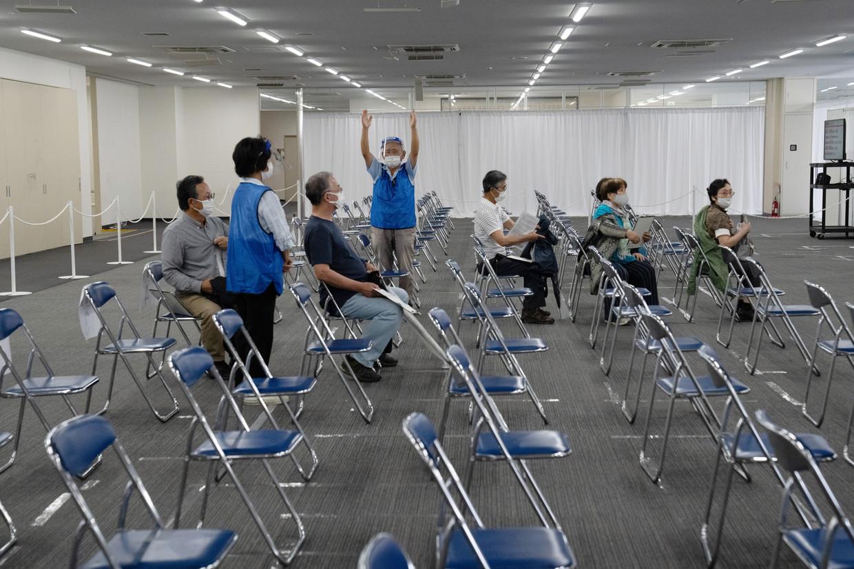 Japanners wachten op hun prik in het pas geopende vaccinatiecentrum in de stad Nagoya.  Beeld Getty Images