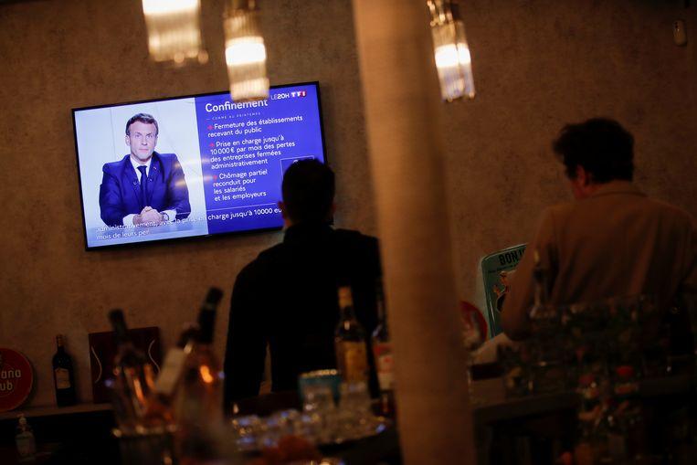 Bezoekers van een restaurant in Parijs kijken naar president Macron, die via de televisie een nieuwe lockdown aankondigt om het coronavirus in te dammen. Beeld Reuters