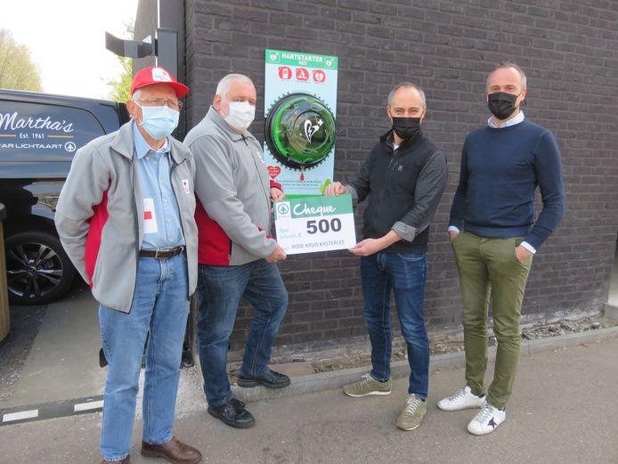 Leo Avonds en Dirk Bockx van het Rode Kruis Kasterlee samen met Guy en Luc Van De Poel van de Spar bij het nieuwe AED-toestel. Er werd ook een cheque van 500 euro geschonken.