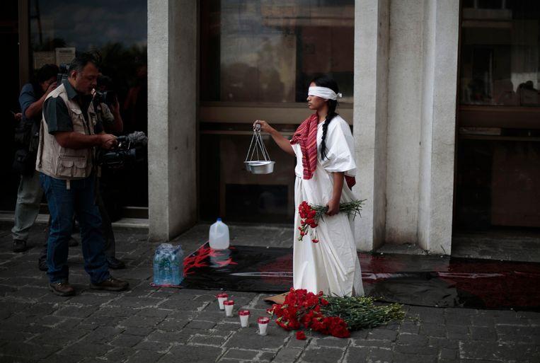 Een vrouw, verkleed als Vrouwe Justitia, protesteert bij het Hooggerechtshof in Guatemala-stad. Archieffoto.