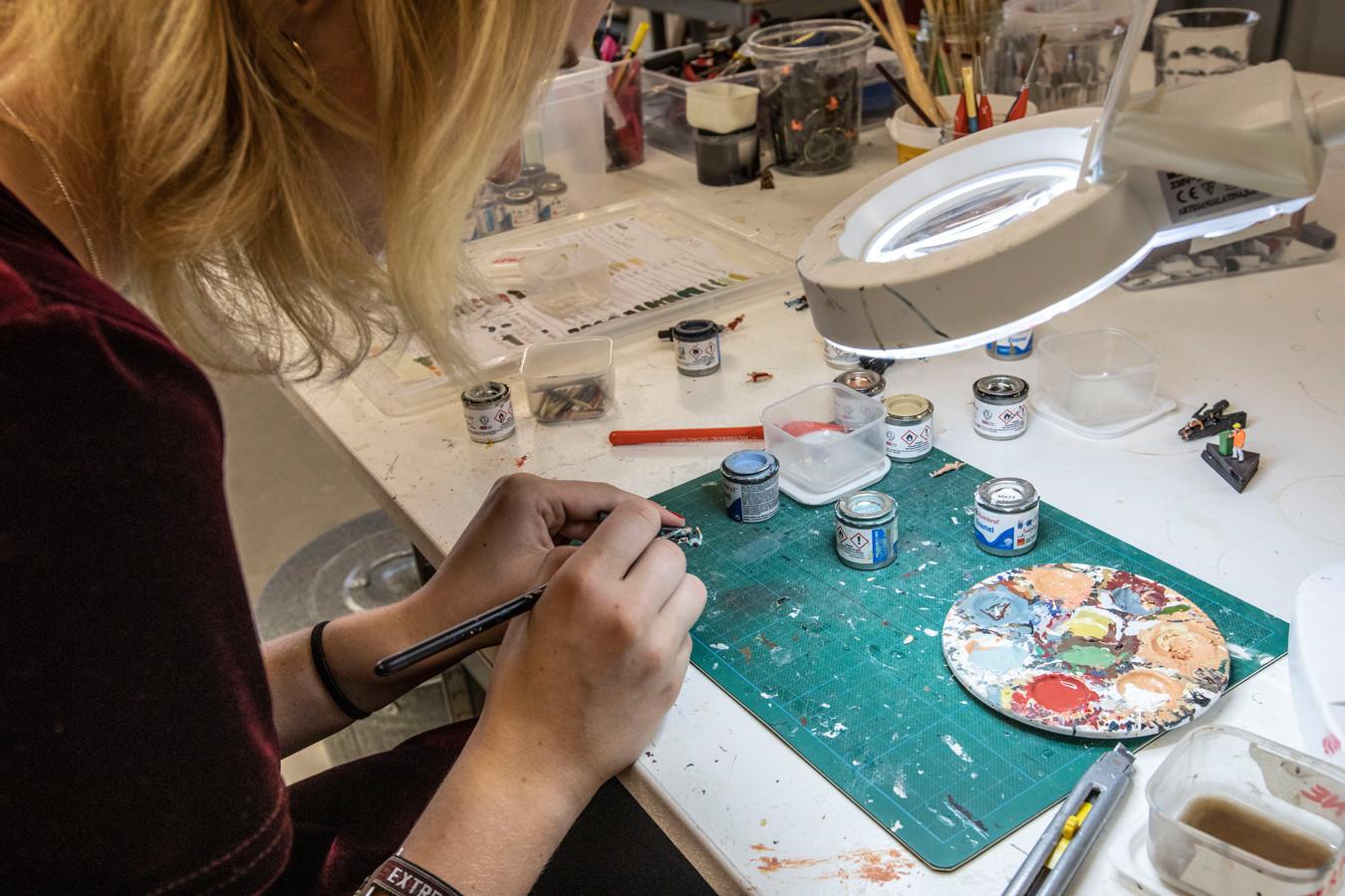 Rosalie Braamkolk werkt in de studio van Rocco Verdult aan een van de miniatuurpoppetjes op de maquette.