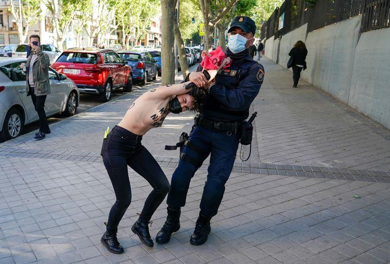 Een lid van de feministische protestbeweging Femen wordt gearresteerd voor het Madrileense kantoor van de extreem-rechtse partij Vox. Beeld Juan Medina / Reuters