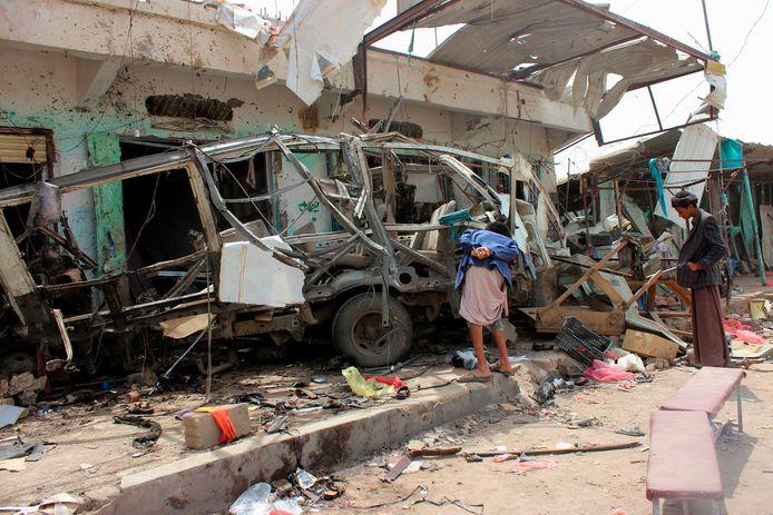 Inwoners van Jemen kijken naar de overblijfselen van de bus die werd gebombardeerd tijdens een luchtaanval.