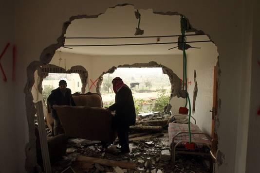 Familieleden in het beschadigde interieur van de woning van Mohammed al-Harub.