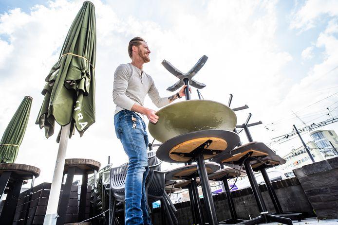 Fabian van Straten zet het terras van Stan&Co, gelegen aan het Arnhemse Willemsplein, alvast neer. Vanaf volgende week kunnen gasten hier weer voor hapjes en drankjes terecht.