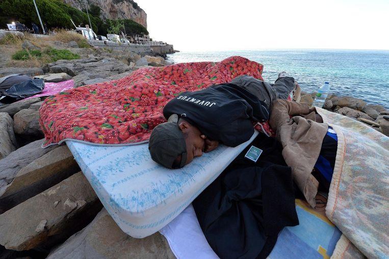 Een vluchteling slaapt op de rotspartijen in Ventimiglia.