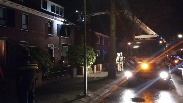 De brandweer inspecteert de woning aan de Cramerstraat, waar een slaapkamer door de brand flinke schade opliep.