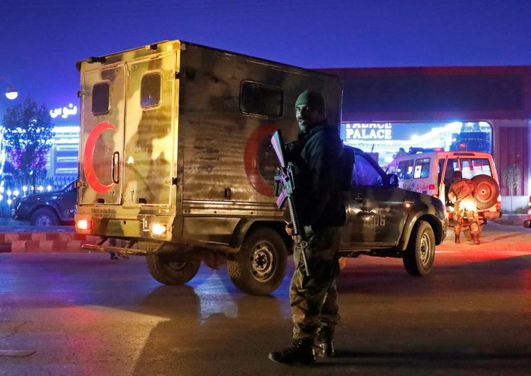 Een Afghaanse politieagent kijkt toe hoe een ambulance gewonden wegvoert na de aanslag. Beeld REUTERS