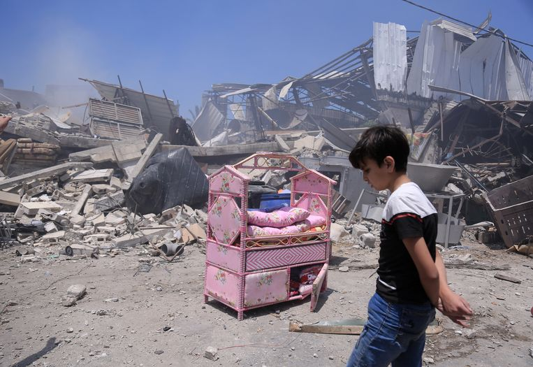 Gaza-stad, 14mei. Een jongen loopt langs het puin van zijn verwoeste huis. Alleen dit fleurig stukje huisraad kon worden gered. Beeld NYT/SAMAR ABU ELOUF