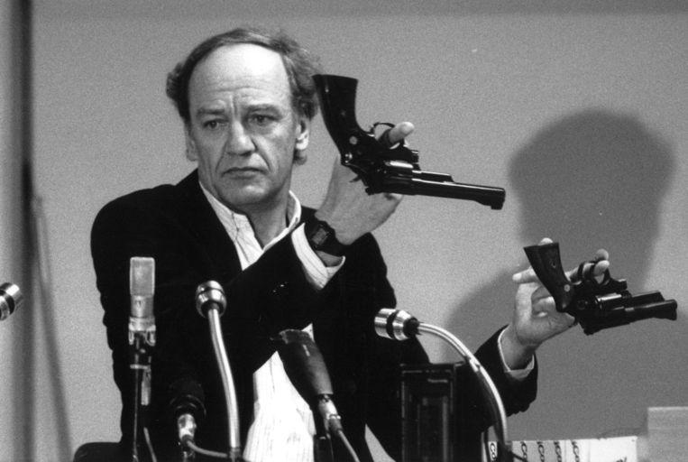 Hans Holmer, hoofd van het onderzoek naar de moord op Olof Palme, toont twee Smith & Wesson-revolvers tijdens een persconferentie in 1986. Beeld via REUTERS