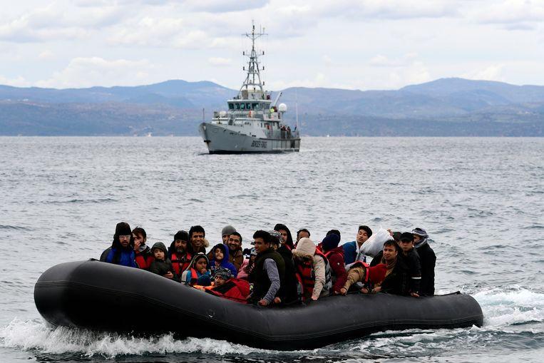 Migranten komen aan bij het Griekse eiland Lesbos, begeleid door een schip van Frontex.  Beeld AP