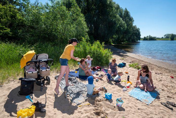 Moeders met hun kinderen op het strandje bij het grindgat. De vakantiesfeer maakt in het weekend in de avonduren plaats voor het festivalgevoel. Dan bevolken honderden jongeren de zandstrook langs de plas.