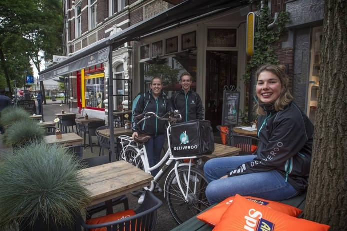 De Eindhovense crew van Deliveroo op het terras bij een van de deelnemers, restaurant Welp aan de Kleine Berg: (vlnr) Sascha Vloet, Nick Buddingh en Janne Verberne met de typsiche Deliveroo-fietstas. Foto Jurriaan Balke/fotomeulenhof
