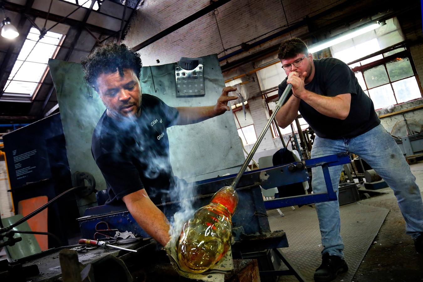 Glasblazers Marco Lopulalan (l) en leerling Ziggy Spronk aan het werk. Zij willen graag het ambacht in stand houden.