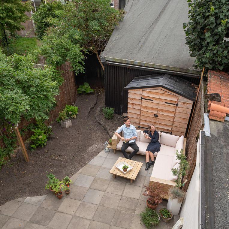 Pepijn en Elkana in hun al deels onttegelde tuintje. Links komen een gazonnetje en planten. Beeld Harry Cock