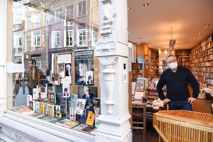 Bij De Vrije Boekhandel staat de deur uitnodigend open, maar wordt de doorgang versperd door een tafel. Achter de tafel staat Guus Welten.