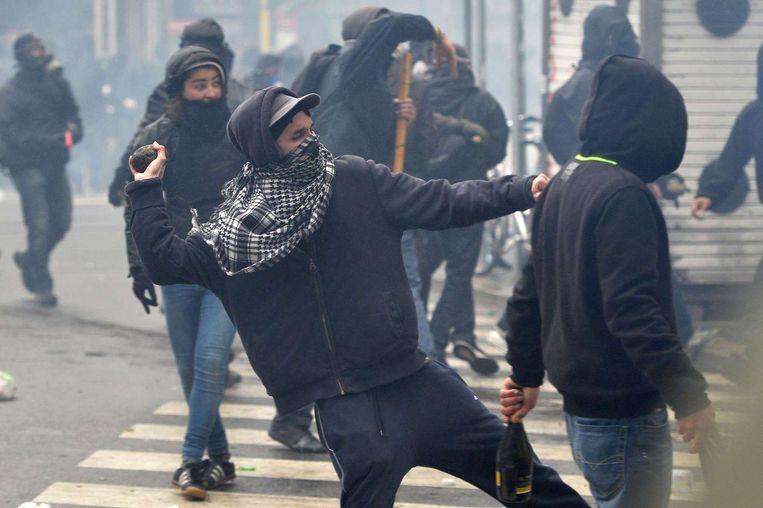 Een demonstrant gooit met een steen naar de politie. Beeld anp