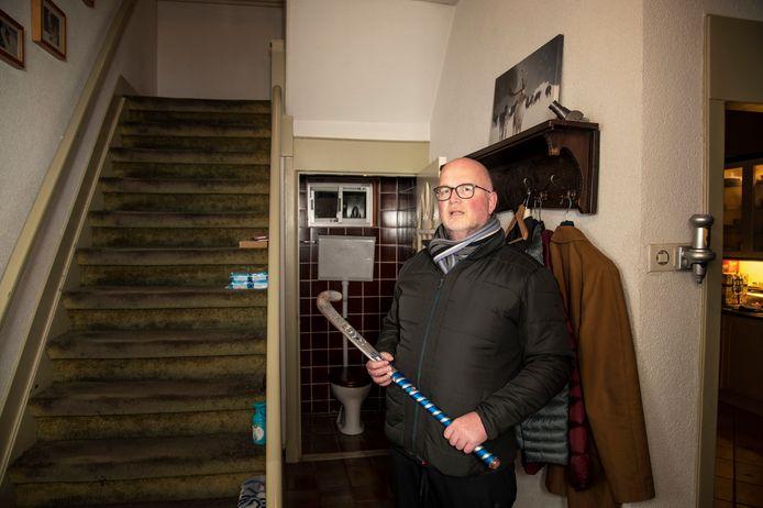 Gert van Lunteren uit Harderwijk in de gang van zijn woning. Achter hem het wc-raampje waardoor de woensdag veroordeelde inbreker in het huis van de Harderwijker kwam.