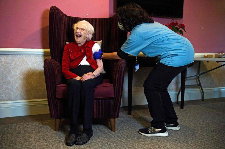 De honderdjarige Ellen Prosser, 'Nell' voor intimi, wordt in Londen gevaccineerd door haar huisarts. Nu de ziekenhuizen overvol zijn, is overgegaan op massale vaccinatie door huisartsen. Beeld AFP